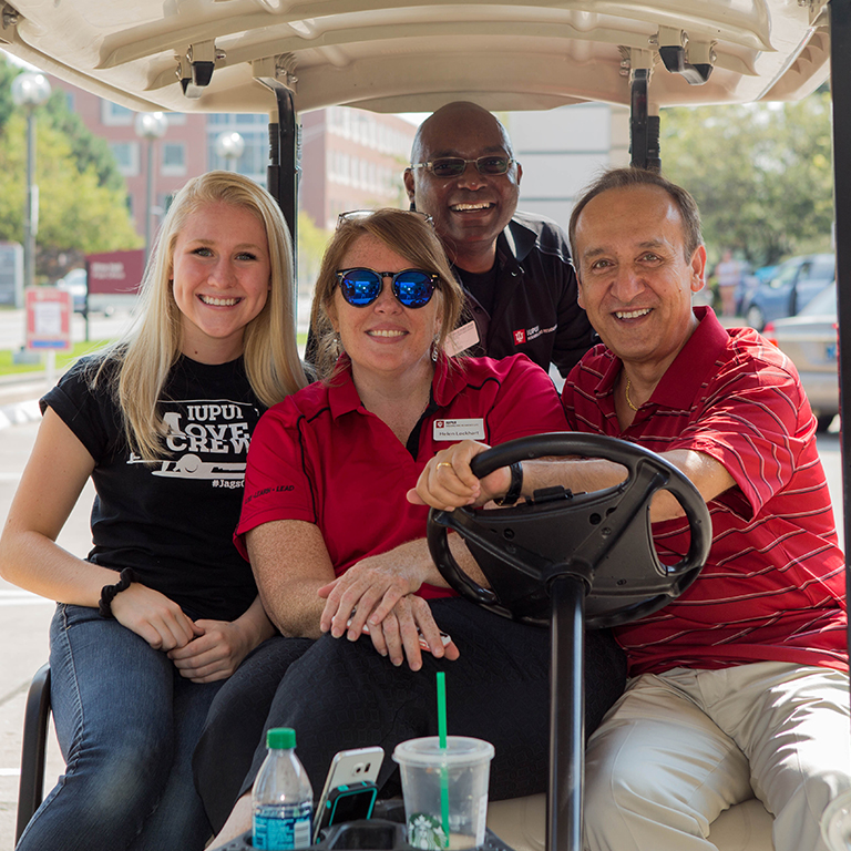 Student Affairs staff in a golf cart at housing move in.