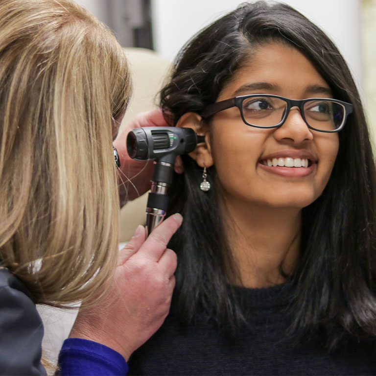 A student having their ear looked at during and exam at the clinic.