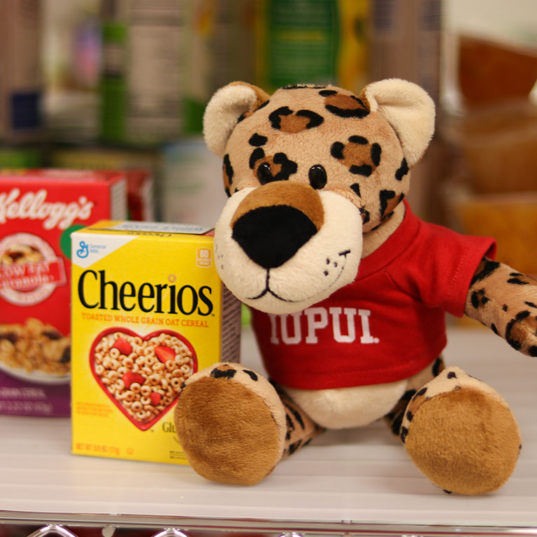 A stuffed animal named Paws posing by a box of cereal.