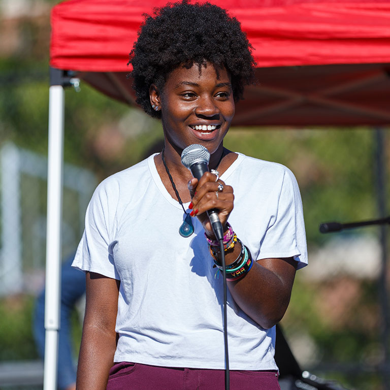 A member of student government at an event talking to students using a mic.