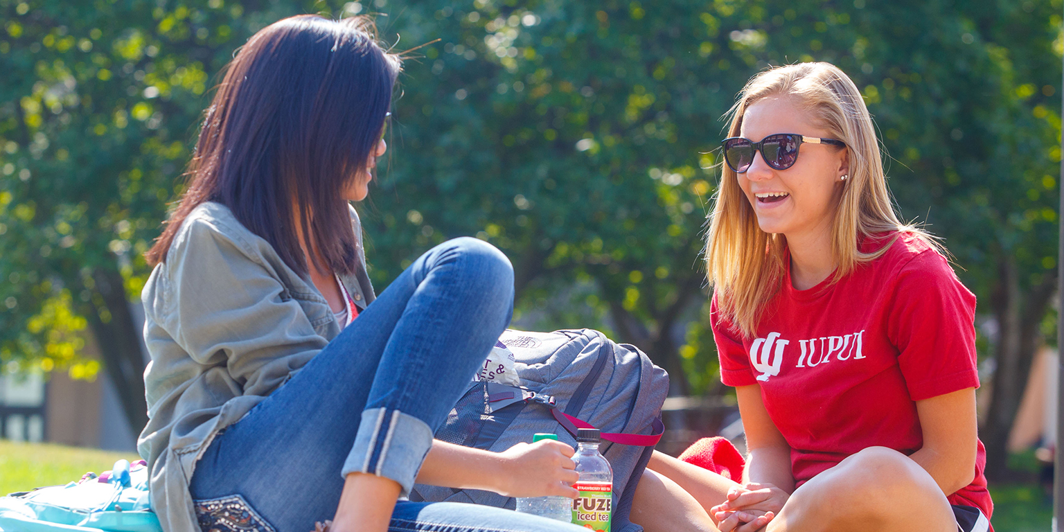 Two students talking on a bench outside in the courtyard outside of Cavanaugh Hall.