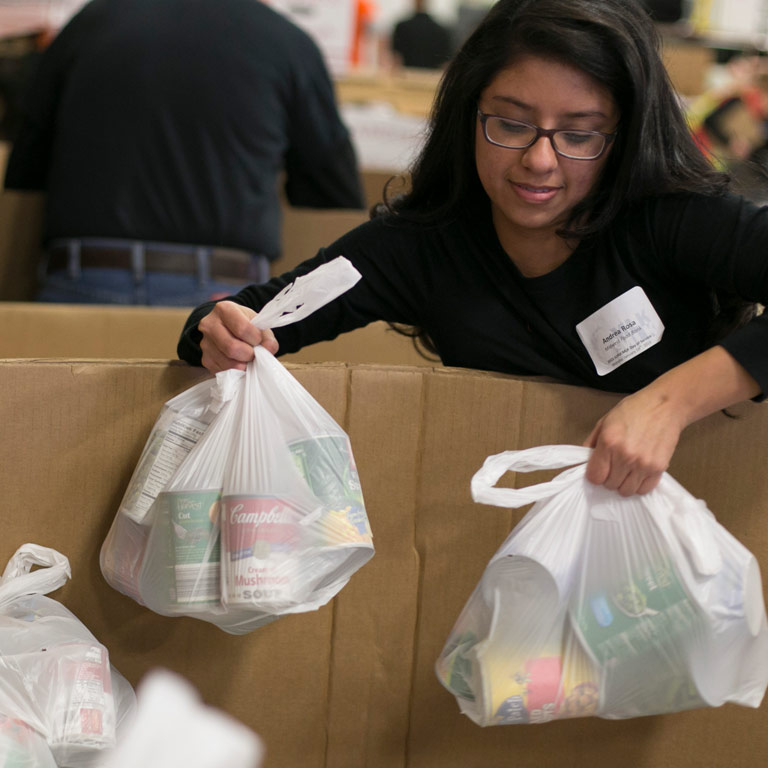 A student carries bags of canned goods