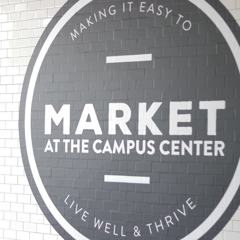 Close up photo of the wall outside of the Market in the Campus Center displaying their logo.