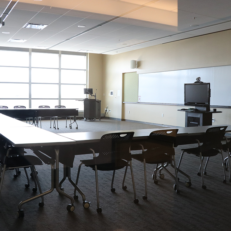 Empty meeting room with audio visual equipment setup in it.