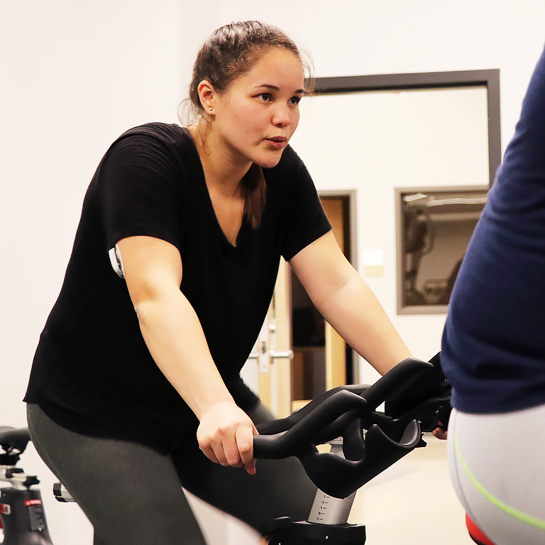 Woman rides an indoor bicycle.