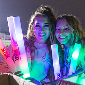 Two students pose with glow sticks at the light up the night event.