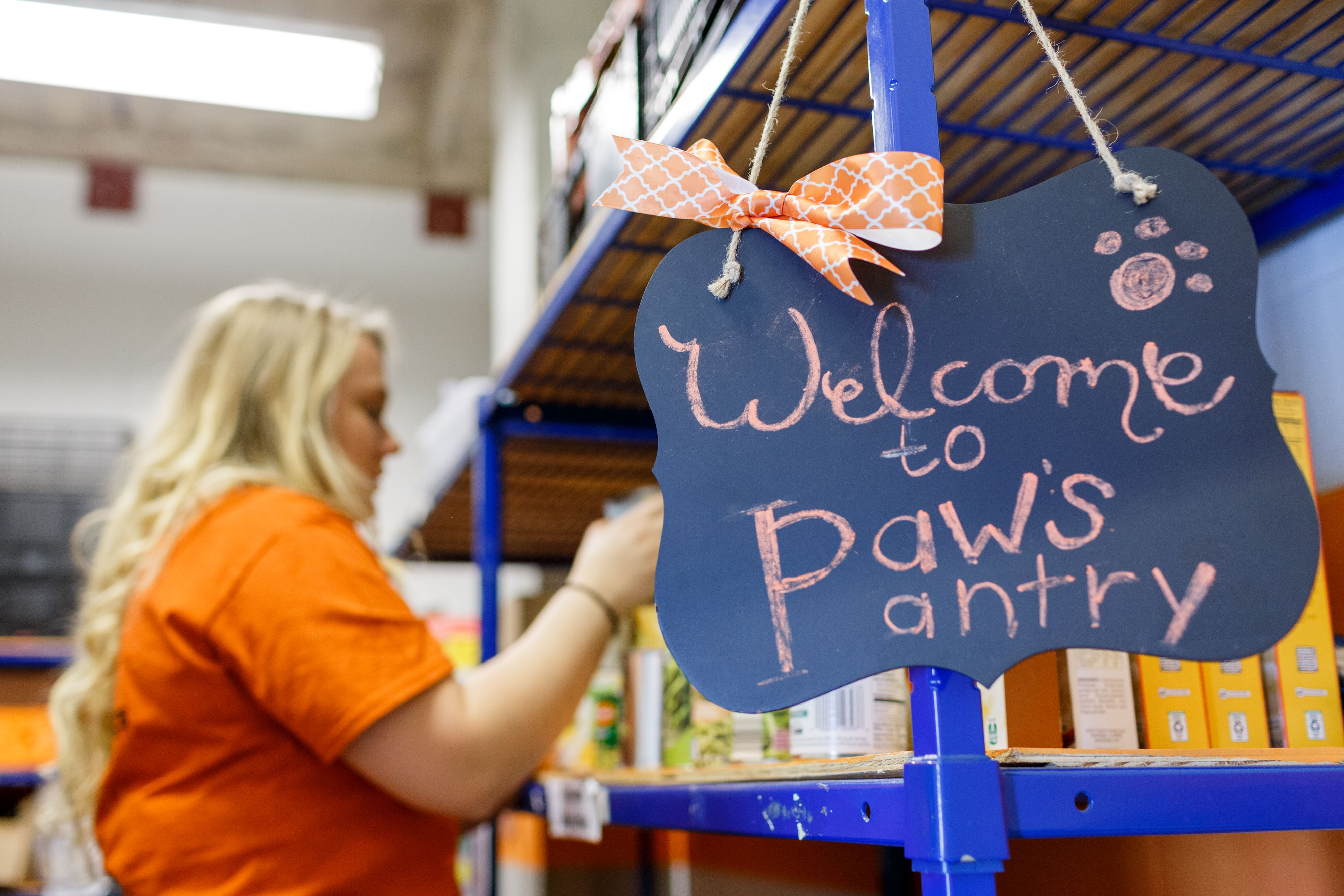 Women stocks shelves with canned goods, sign in the foreground says Welcome to Paw's Pantry.