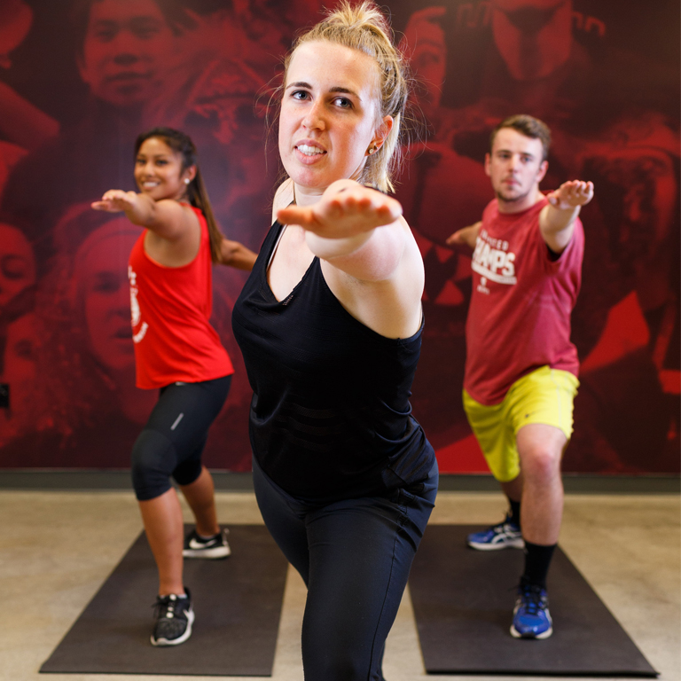 Three students do the warrior yoga pose.