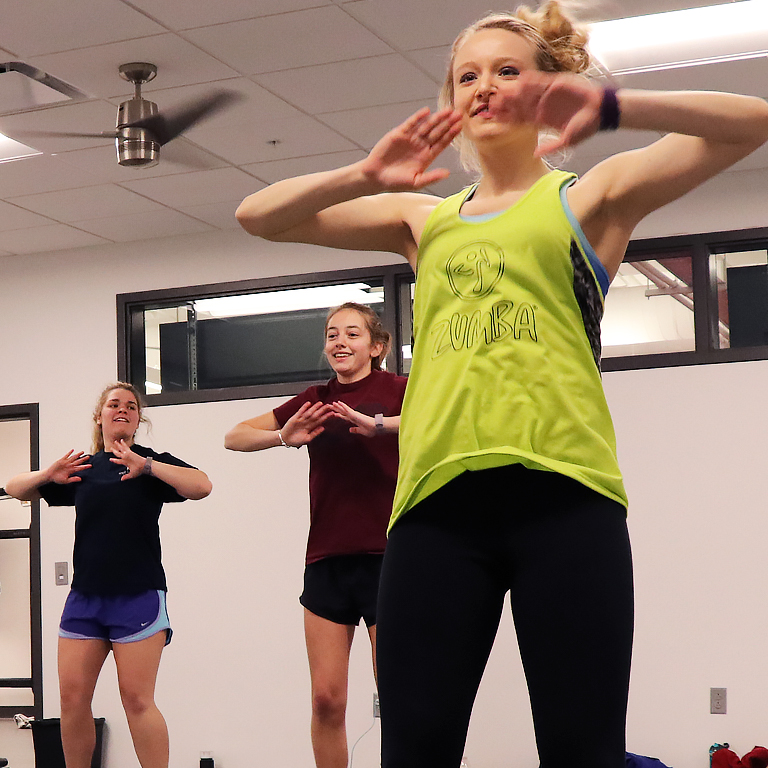 A group of students do Zumba in a dance studio.