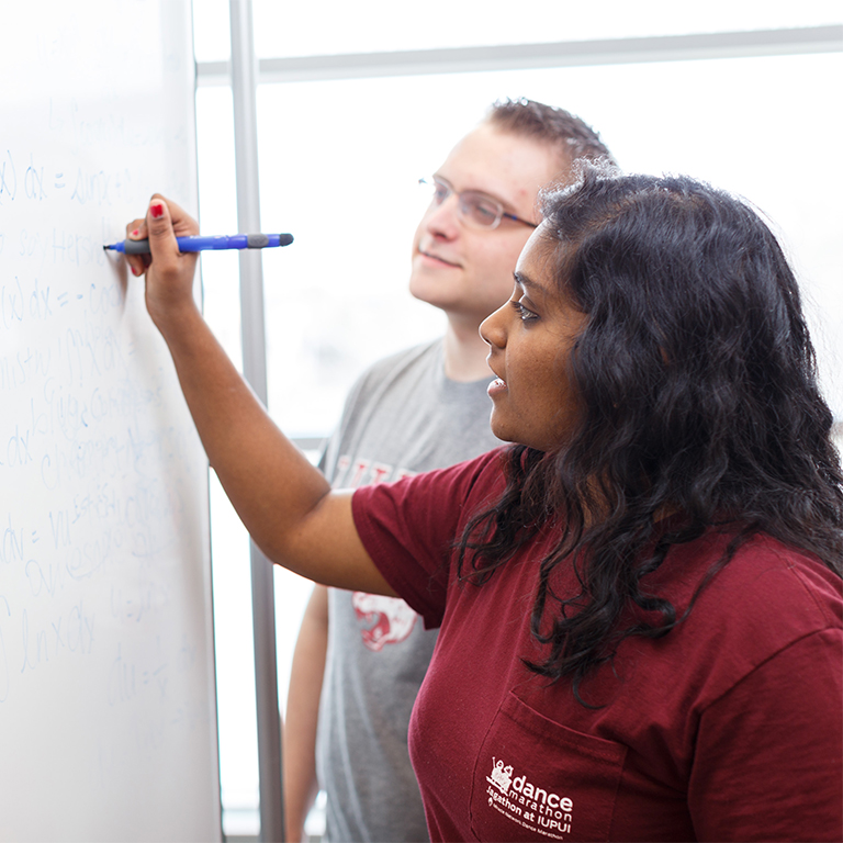 Two students write on a white board in the cube