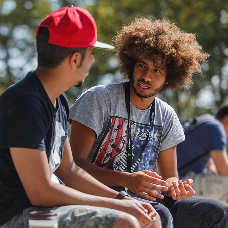 Two students talk outside of the campus center.