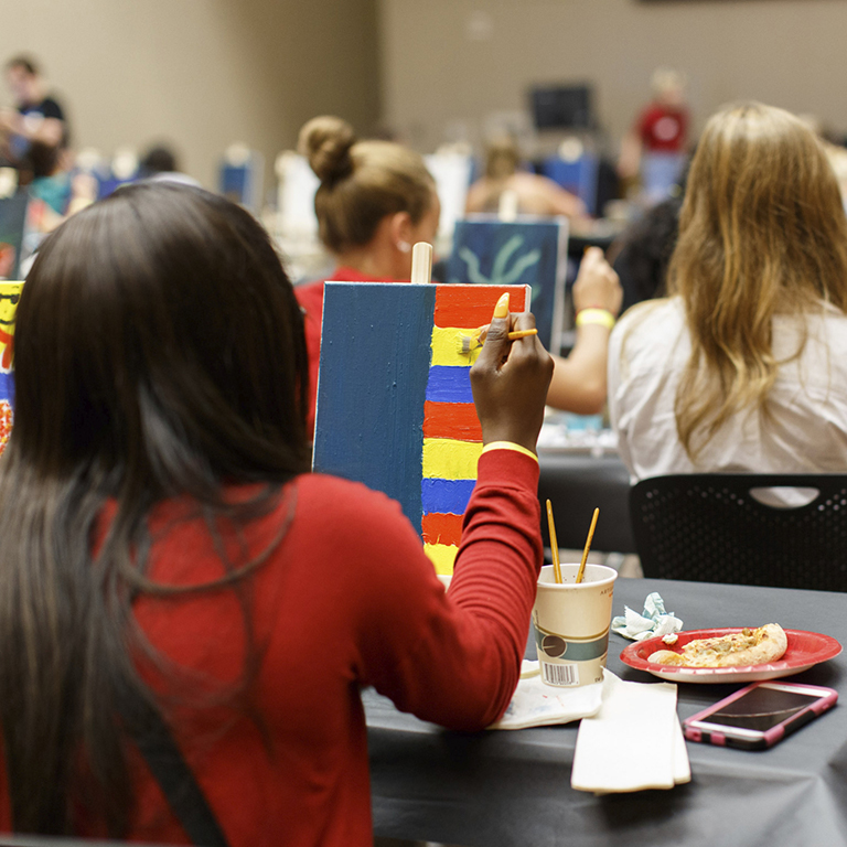 Student paints at a sapb event.