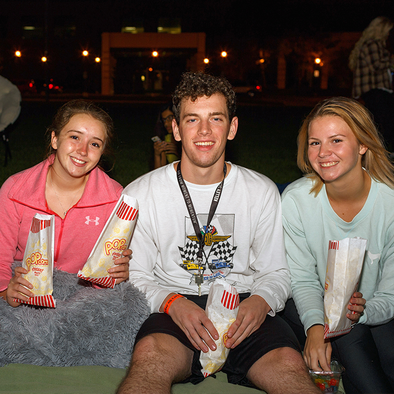 Students hold popcorn at movie night.