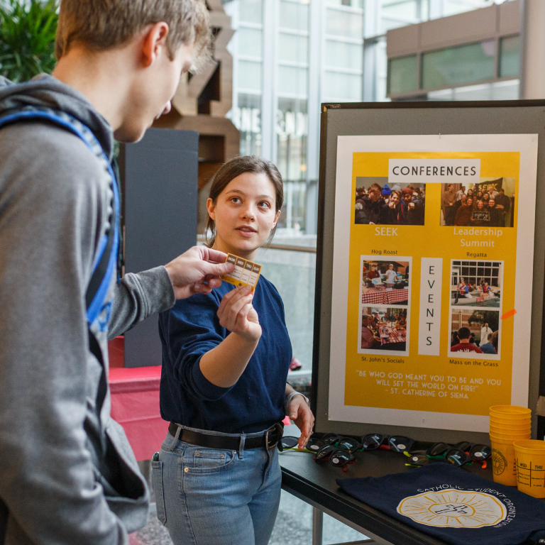 A student with a dog wears reindeer antlers.