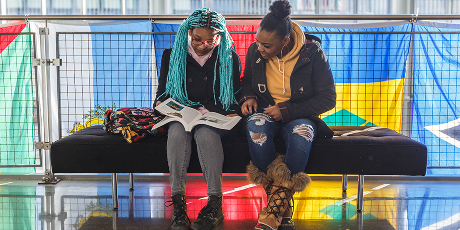 Two students sit in the campus center look at a book.