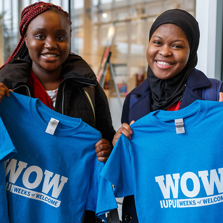 Two students holding up their custom made WOW shirts.
