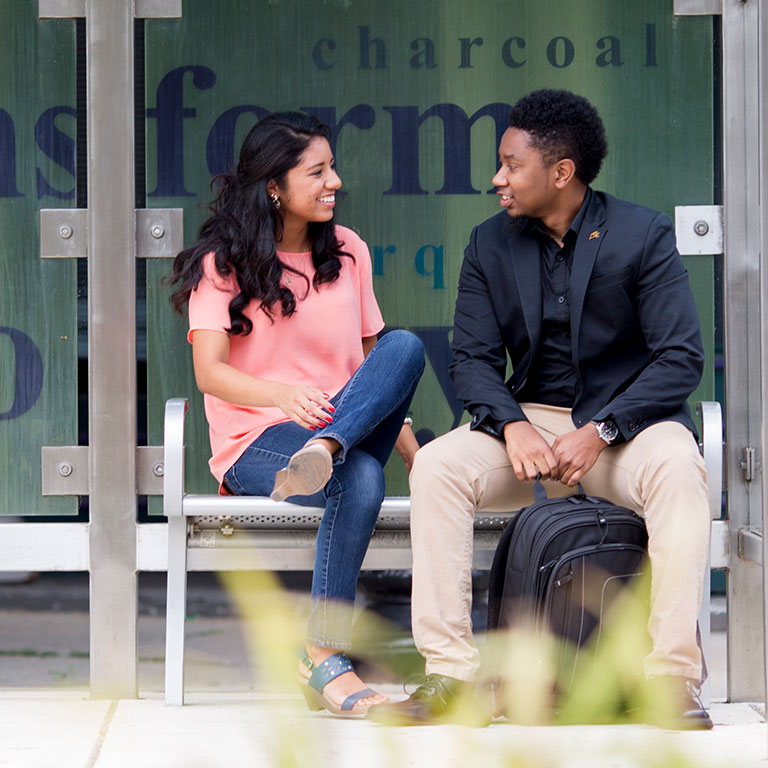 Two students engaging in conversation at a bus stop.