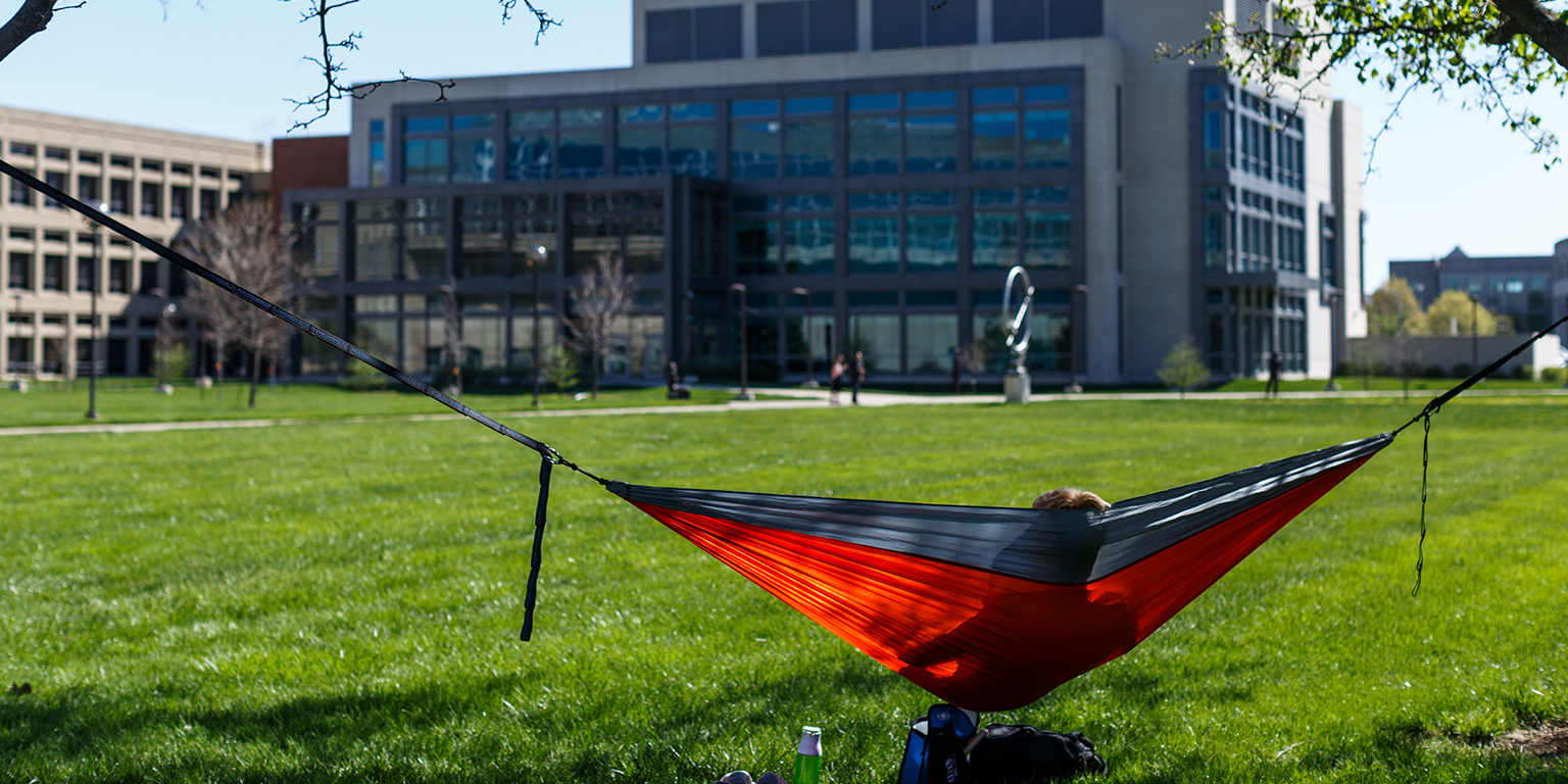 Student sits in a hammock in the south meadow.