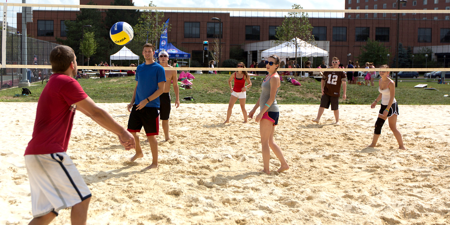 Students play sand volleyball.