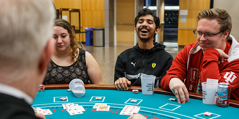 Three students playing poker at a casino event.
