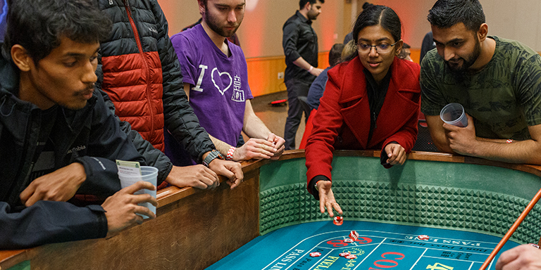 Students rolling dice at a casino event.